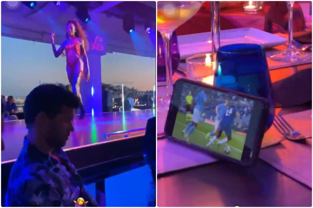 While scantily-clad beauties dance away behind him, a Chelsea icon watches the Champions League final on his phone.